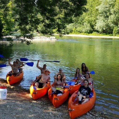 Grupo de jóvenes en canoa en playa fluvial en descenso del sella